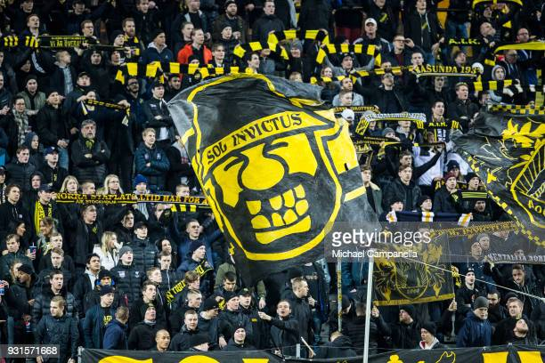 AIK supporters waving flags and holding up scarves during a Swedish Cup quarter final match between AIK and Orebro SK at Friends arena on March 13...