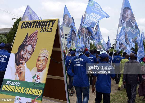 Supporters waving flags walk past a campaign sign to mobilize support for the reelection of Nigerian President Goodluck Jonathan and candidate of the...