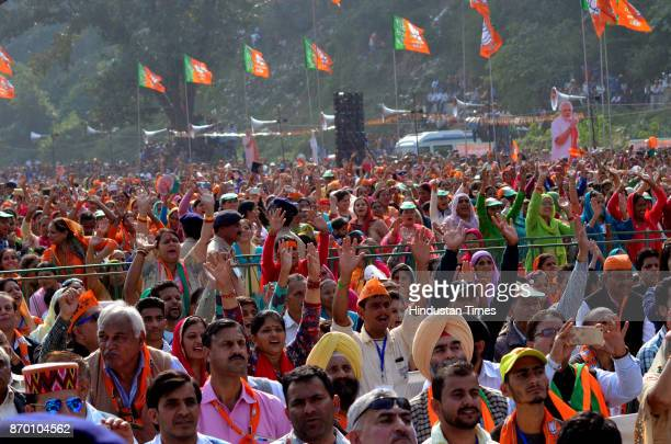BJP supporters waving hands during a BJP Parivartan Rally addressed by Prime Minister Narendra Modi at Rait on November 4 2017 in Dharamsala India PM...