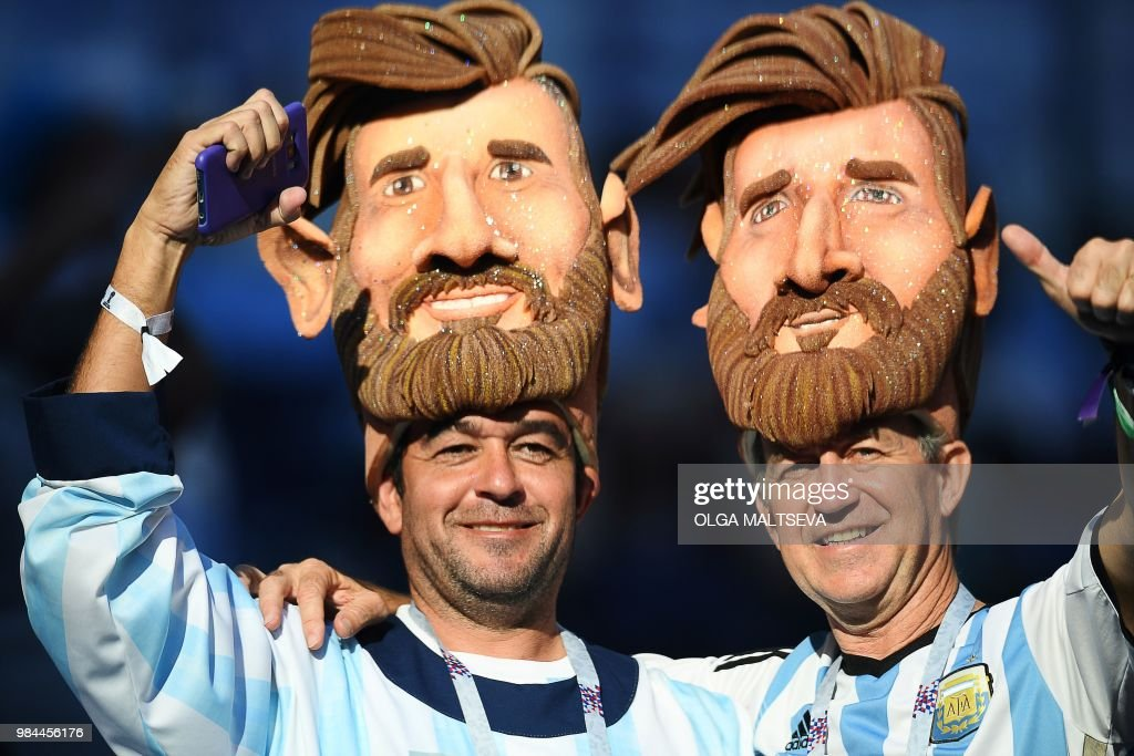 TOPSHOT - Supporters wear masks depicting Argentina's forward Lionel Messi before the Russia 2018 World Cup Group D football match between Nigeria and Argentina at the Saint Petersburg Stadium in Saint Petersburg on June 26, 2018. (Photo by OLGA MALTSEVA / AFP) / RESTRICTED