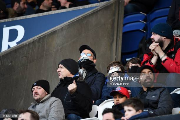 Supporters wear protective masks at the Parc des Princes stadium in Paris, on February 29, 2020 before the Ligue 1 football match between Paris...