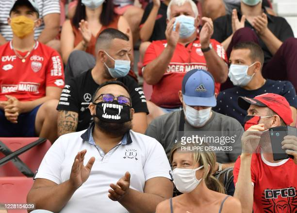 Supporters wearing face masks attend the French L1 football match between Dijon FCO and Angers on August 22 at the Gaston Gerard stadium in Dijon,...