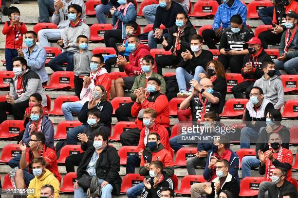 Supporters wearing face masks attend the French Ligue 1 football match between Stade Rennais and Montpellier, at the Roazhon Park stadium in Rennes,...