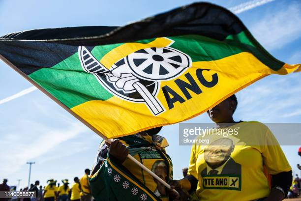 Supporters wearing party colors wave a flag during an African National Congress party campaign event in Bloemfontein South Africa on Sunday April 7...