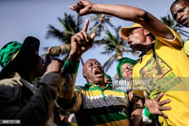 Supporters wearing the colours of the African National Congress sing and dance, on June 8, 2018 outside the High Court, in Durban, during a rally in...
