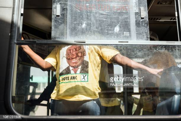 TOPSHOT Supporters wearing tshirts depicting South African President Cyril Ramaphosa arrive by bus at the African National Congress 107th anniversary...