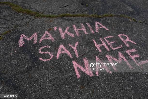 Supporters write messages in chalk at a vigil in Columbus, Ohio on April 21, 2021 in memory of MaKhia Bryant who was shot and killed by a Columbus...
