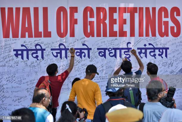 BJP supporters write their messages during an event Wall of Greetings organised by BJP at Rajiv Chowk on May 28 2019 in New Delhi India