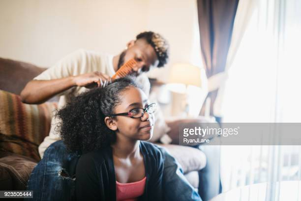 supportive father helps daughter braid hair - braided hair stock pictures, royalty-free photos & images