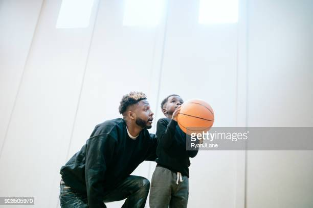 supportive father plays basketball with son - basketball sport stock pictures, royalty-free photos & images