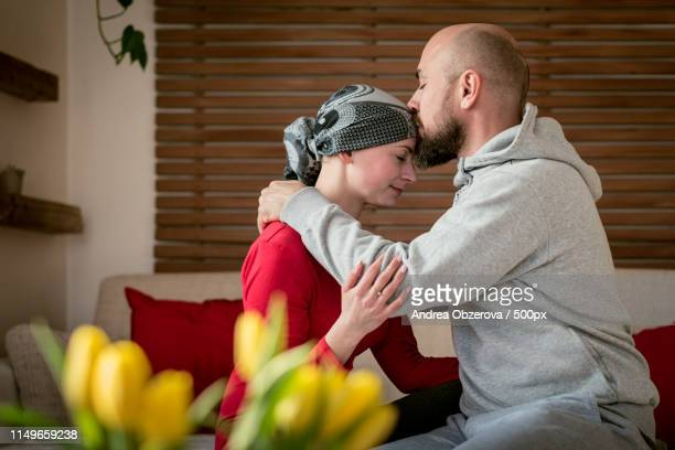 supportive husband kissing his wife, cancer patient, after treatment in hospital cancer and - mastektomie stock-fotos und bilder