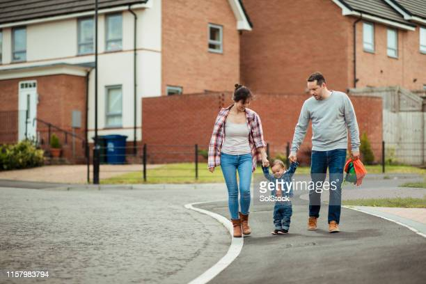 supportive mother and father - walking stock pictures, royalty-free photos & images