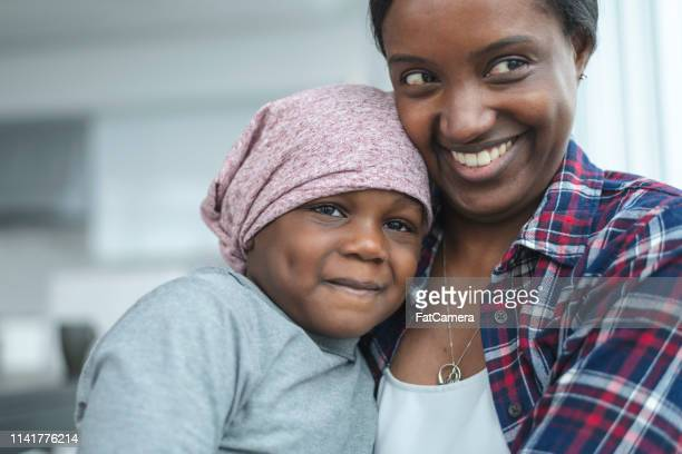 supportive mother holds child with cancer - cancer illness stock pictures, royalty-free photos & images