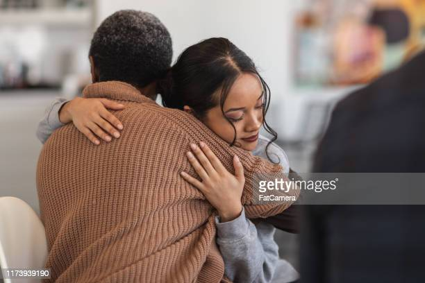 supportive women hug while attending a group therapy session - grief stock pictures, royalty-free photos & images