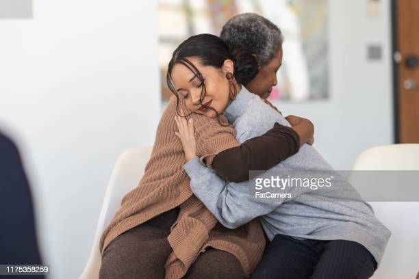 supportive women hug while attending a group therapy session - victim stock pictures, royalty-free photos & images