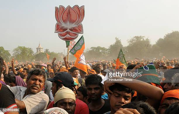 BJP supports with party flags and symbol cutouts during election campaign rally of Prime Minister Narendra Damodardas Modi before third phase of...