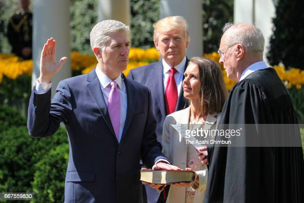 US Supreme Court Associate Justice Anthony Kennedy administers the judicial oath to Judge Neil Gorsuch as his wife Marie Louise Gorsuch holds a bible...