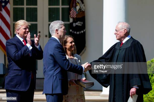 S Supreme Court Associate Justice Anthony Kennedy shakes hands with Associate Justice Neil Gorsuch as his wife Marie Louise Gorshuch and President...