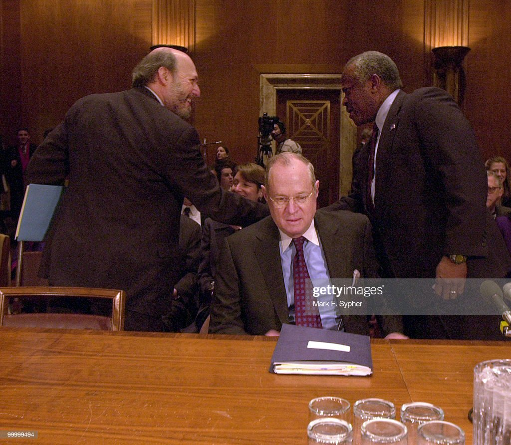 Supreme Court Associate Justice Anthony Kennedy sits down while Supreme Court Associate Justice Clarence Thomas (right) greets the Architect of the Capitol, Alan M. Hantman.