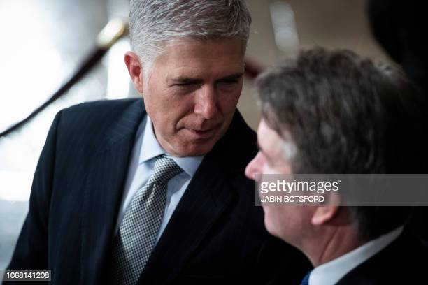 Supreme Court Associate Justice Neil M Gorsuch and Associate Justice Brett M Kavanaugh await the arrival of former US president George HW Bush at the...