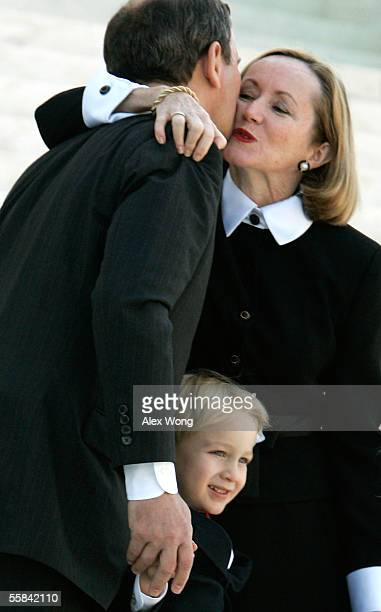 Supreme Court Chief Justice John G. Robers kisses his wife, Jane, as his son, Jack, stands with them after an investiture ceremony at the Supreme...