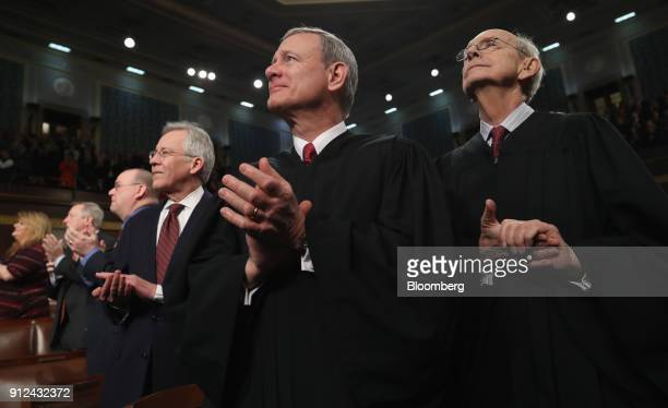 Supreme Court Chief Justice John Roberts center and Stephen Breyer associate justice of the Supreme Court right applaud during a State of the Union...