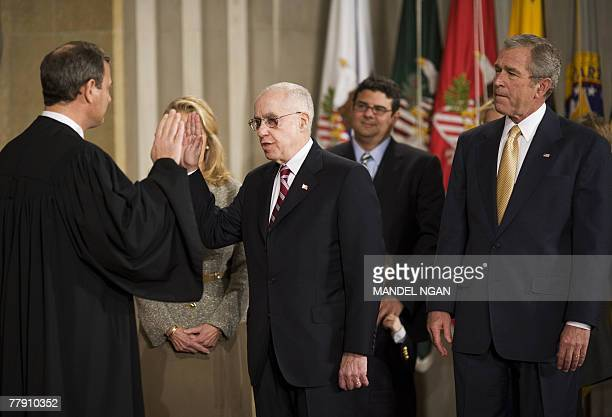 Supreme Court Chief Justice John Roberts gives the oath of office to Attorney General Michael Mukasey, as US President George W. Bush watches, during...