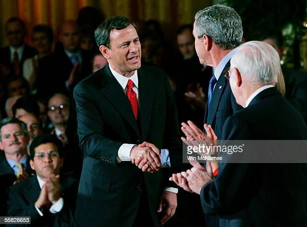 Supreme Court Chief Justice John Roberts shakes hands with U.S. President George W. Bush as U.S. Supreme Court Associate Justice John Paul Stevens...