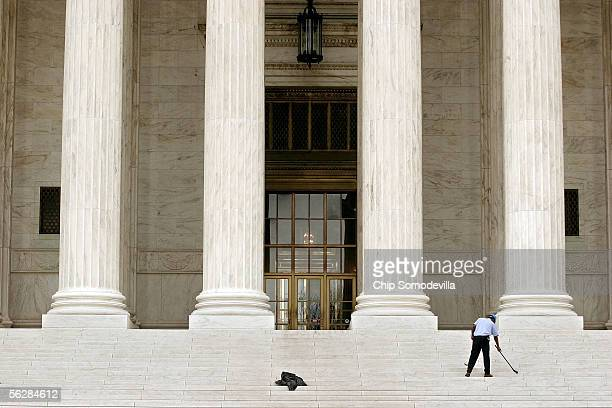 Supreme Court employee sweeps up the last bits of broken stone after a basketballsized piece of the United States Supreme Court's dentil mould broke...