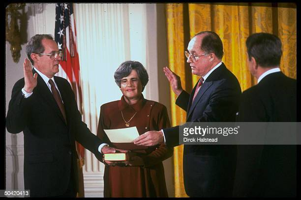 Supreme Court Justice Anthony Kennedy being swornin by Chief Justice Rehnquist as wife Mary holds bible Pres Reagan looks on