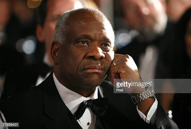 Supreme Court Justice Clarence Thomas listens to U.S. President George W. Bush speak at the the Federalist Society's 25th annual gala at the...