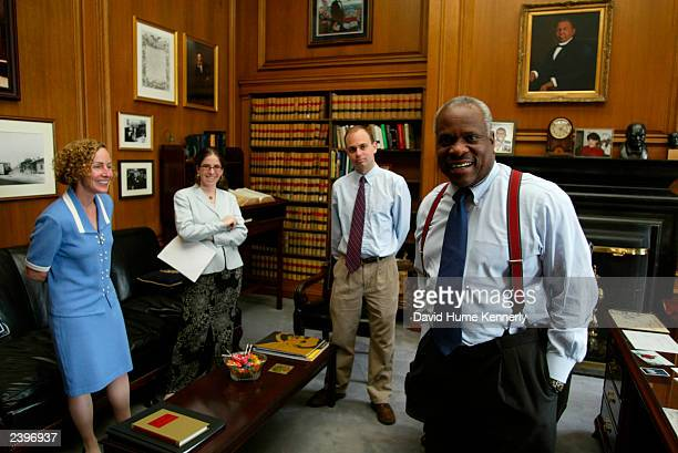 US Supreme Court Justice Clarence Thomas stands in his chambers with three of his clerks at the Supreme Court June 18 2002 in Washington DC