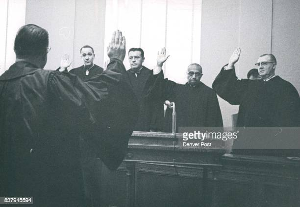 Supreme Court Justice Edward Day administers the oath of office to from let Denver District Judges Merle Knous Ed Byrne James Flanigan and Gerald...