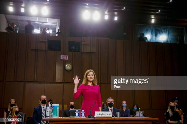 Supreme Court Justice nominee Judge Amy Coney Barrett stands as she is sworn in during the Senate Judiciary Committee confirmation hearing for...