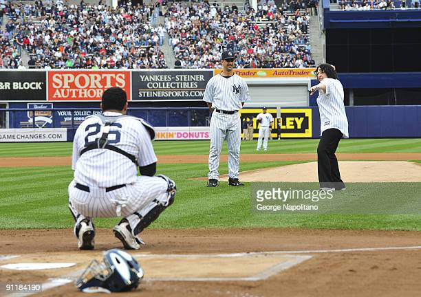 Supreme court Justice Sonia Sotomayor is accompanied by New York Yankees catcher Jorge Posada as she throws out the first ball at Yankee Stadium on...