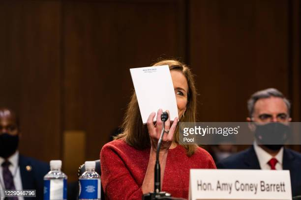 Supreme Court nominee Judge Amy Coney Barrett holds up an empty notepad before the Senate Judiciary Committee on the second day of her Supreme Court...
