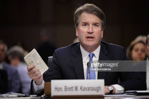 Supreme Court nominee Judge Brett Kavanaugh holds up a small copy of the US Constitution while answering questions before the Senate Judiciary...