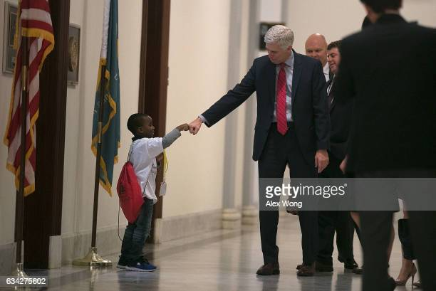 S Supreme Court nominee Judge Neil Gorsuch fistbumps fouryearold Charles Marshall III of Dover Delaware in the hallway as he arrives for a meeting...