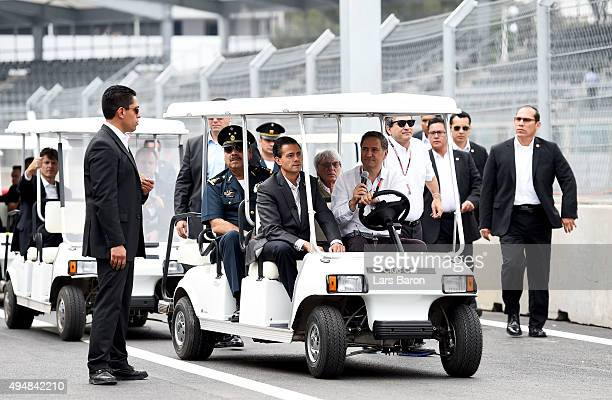 F1 supremo Bernie Ecclestone arrives in the pit lane with the President of Mexico Enrique Pena Nieto during previews to the Formula One Grand Prix of...