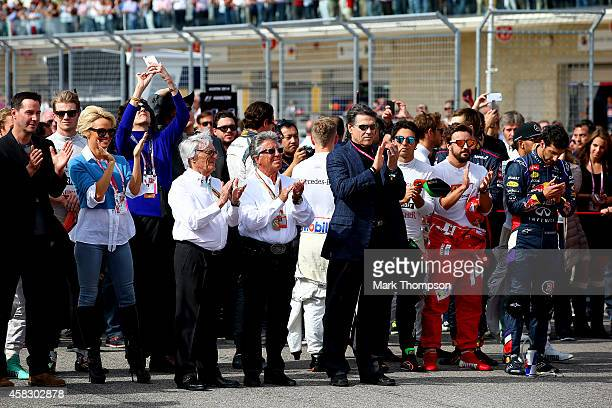 F1 supremo Bernie Ecclestone former champion Mario Andretti actors Keanu Reeves and Pamela Anderson and the drivers stand for the national anthem...