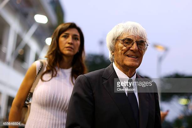 F1 supremo Bernie Ecclestone walks through the paddock with his wife Fabiana Flosi during previews ahead of the Singapore Formula One Grand Prix at...