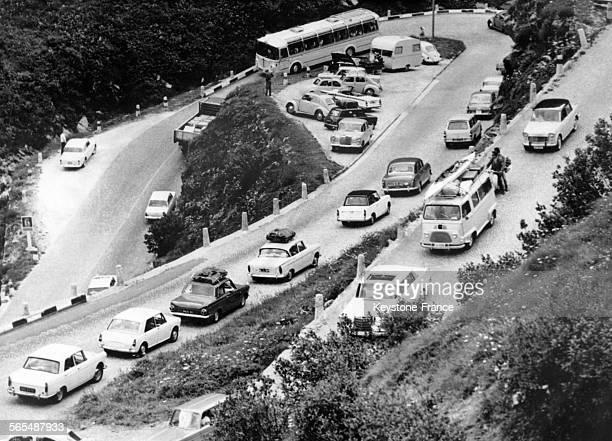 Sur la route de montagne avec des virages en lacets les véhicules des vacanciers roulent au ralenti en Suisse le 17 juillet 1964