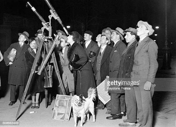 Sur les quais de Seine des astronomes ambulants proposent à des badauds de regarder la lune avec des télescopes pour 10 sous le 1er avril 1931 à...