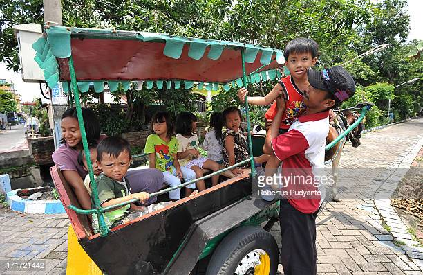 Surabaya, Indonesia - Slamet and his dokar at work carrying the kids went around the district. Slamet has to taking good care of his passengers...