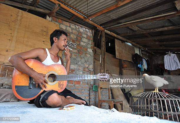 Surabaya, Indonesia - Slamet playing guitar and smoking while take his time off. In the 1960s, the traditional dokar, or horse cart, was one of the...