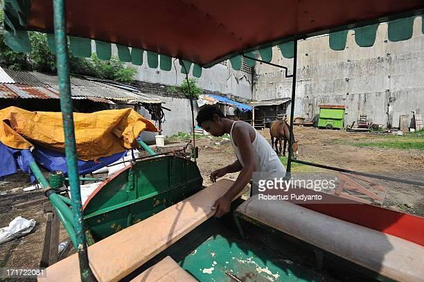 Surabaya, Indonesia - Slamet prepare the dokar before start working around. In the 1960s, the traditional dokar, or horse cart, was one of the main...