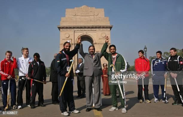 Suresh Kalmadi president of Indian Olympic Association holds hands of Indian hockey team captain Rajpal Singh left and Pakistan hockey team captain...