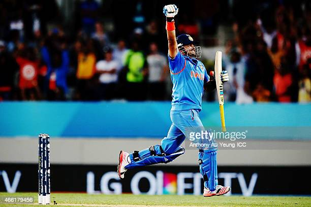 Suresh Raina of India celebrates after scoring a century during the 2015 ICC Cricket World Cup match between India and Zimbabwe at Eden Park on March...