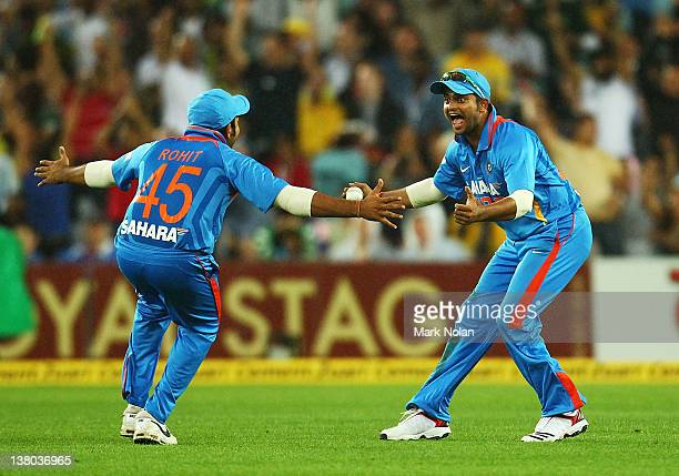 Suresh Raina of India celebrates catching David Warner of Australia with team mate Rohit Sharma during the International Twenty20 match between...