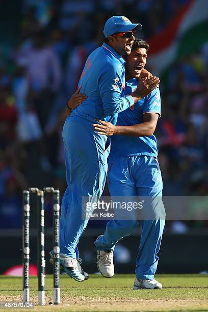 Suresh Raina of India congratulates Umesh Yadav of India as he celebrates taking the wicket of Aaron Finch of Australia during the 2015 Cricket World...